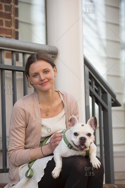 Portrait of Caucasian woman sitting on stoop holding dog