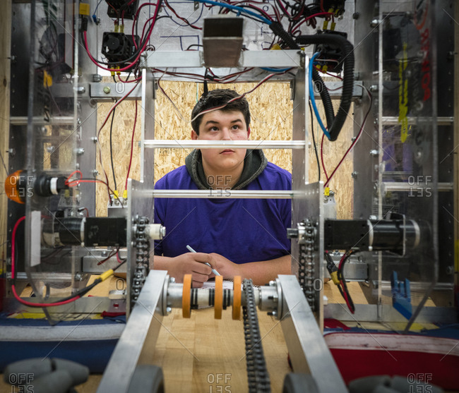 Caucasian boy with notebook examining robotics at school