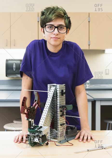 Native American girl posing with robotics at school