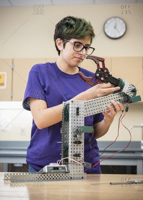 Native American girl adjusting robotics at school