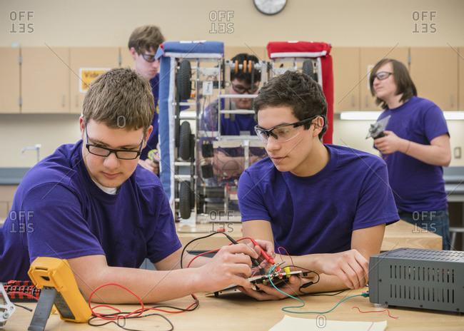Caucasian boys testing electronics at school