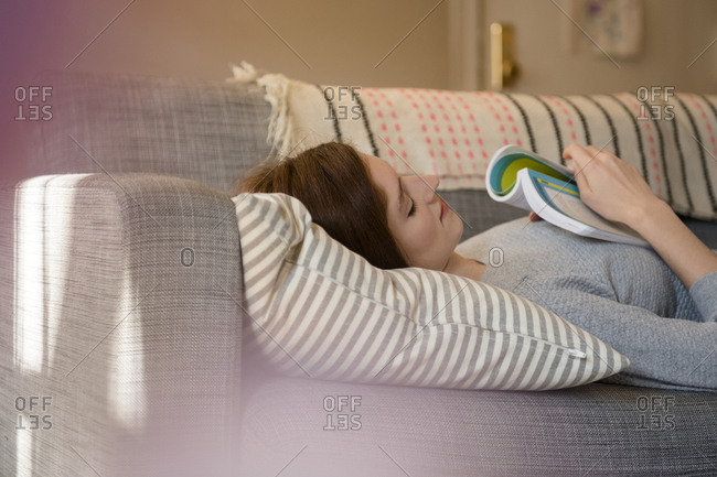 Caucasian woman napping on sofa holding book