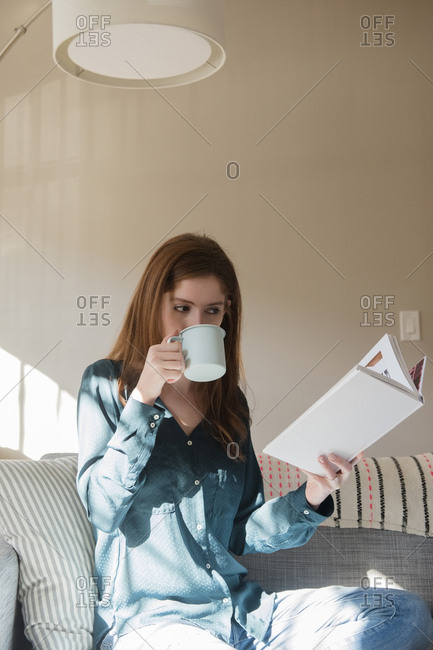 Caucasian woman sitting on sofa drinking coffee and reading book