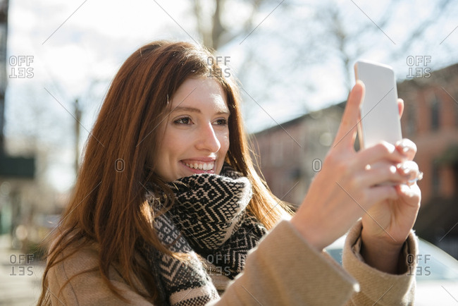 Caucasian woman wearing scarf posing for cell phone selfie
