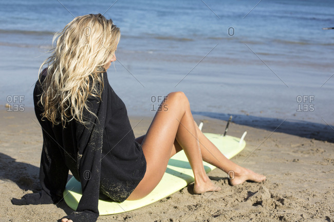 Caucasian woman sitting on surfboard on beach