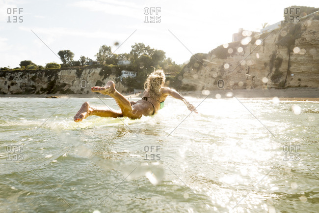Caucasian woman paddling on surfboard in ocean
