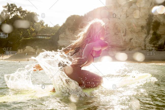 Caucasian woman kneeling on surfboard in ocean and paddling