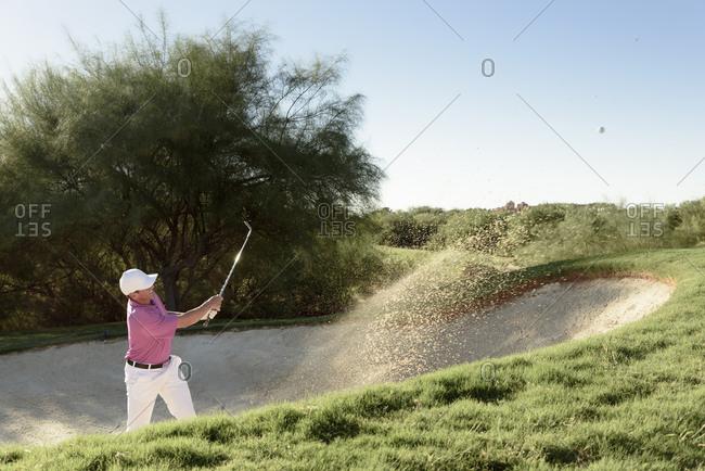 Hispanic golfer hitting ball in sand trap