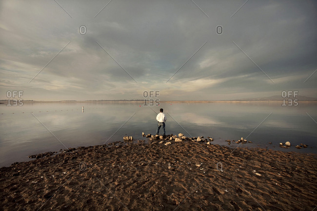 Distant man fishing on beach