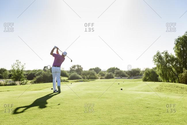 Hispanic golfer teeing off on golf course