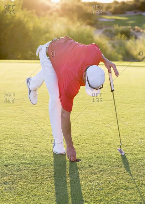 Hispanic golfer reaching into hole on golf course