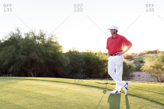 Hispanic golfer waiting on golf course