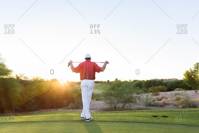 Hispanic golfer waiting on golf course