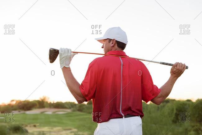 Hispanic golfer holding golf club on shoulders