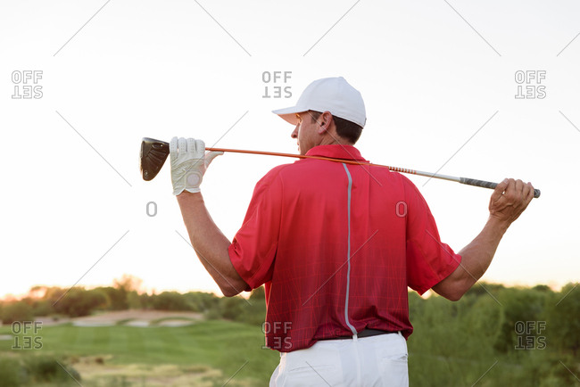 Hispanic golfer holding golf club on shoulders
