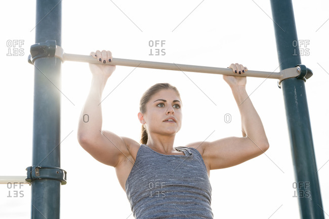 Hispanic woman doing chin-up outdoors