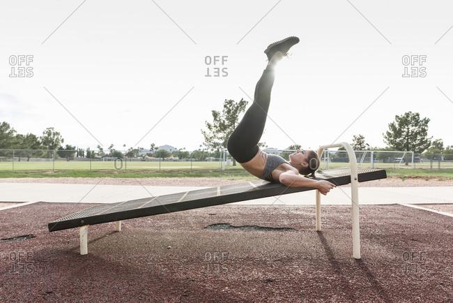 Hispanic woman doing leg lifts outdoors