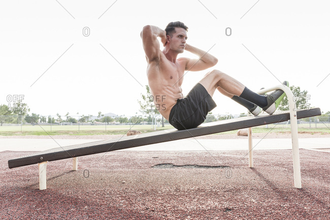 Caucasian man doing sit-ups outdoors