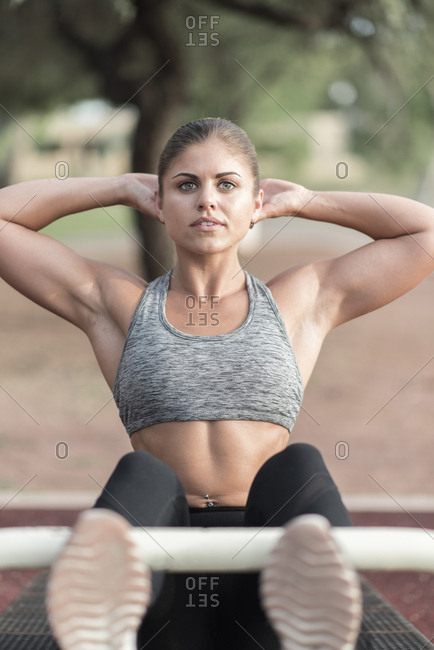 Hispanic woman doing sit-ups outdoors