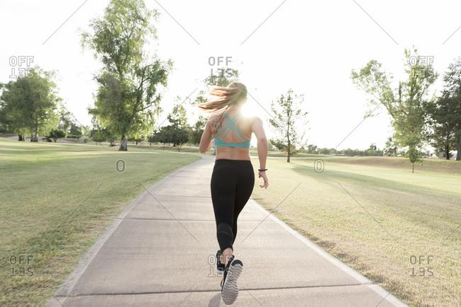 Hispanic woman running on path in park