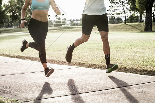 Couple running on path in park