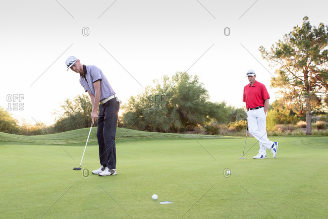 Man watching friend putting on golf course