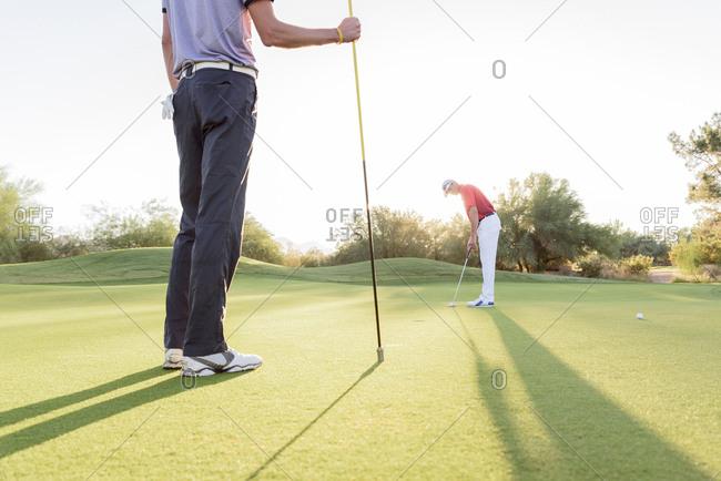 Hispanic man watching friend on golf course