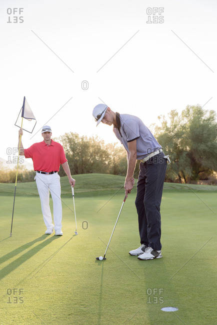 Hispanic man watching friend on golf course