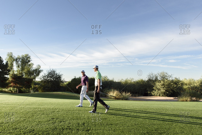 Friends walking on golf course