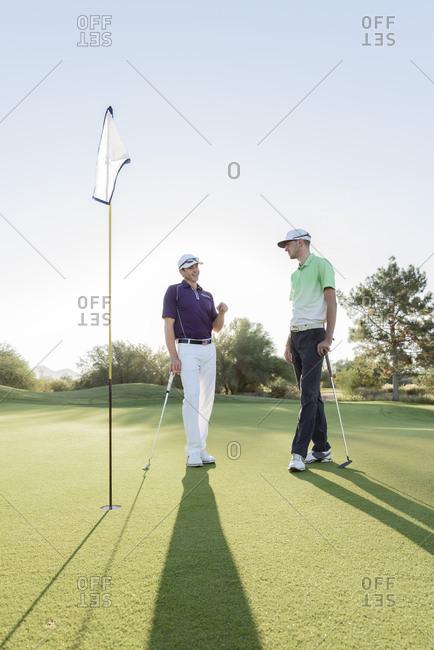 Friends talking on golf course