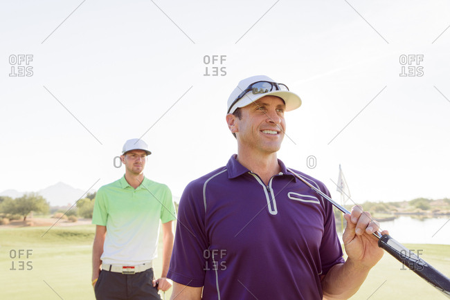 Friends holding golf clubs on golf course