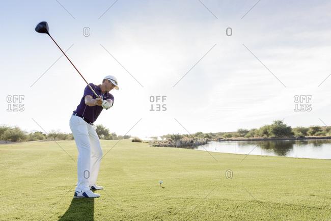Hispanic man teeing off on golf course