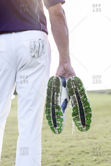 Hispanic man hold golf shoes covered with grass