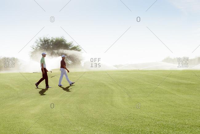 Friends walking on golf course near sprinklers