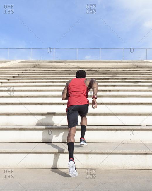 African American man running on bleachers