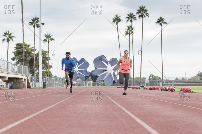 Man and woman running with parachutes on track