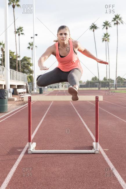 Hispanic woman jumping over hurdle