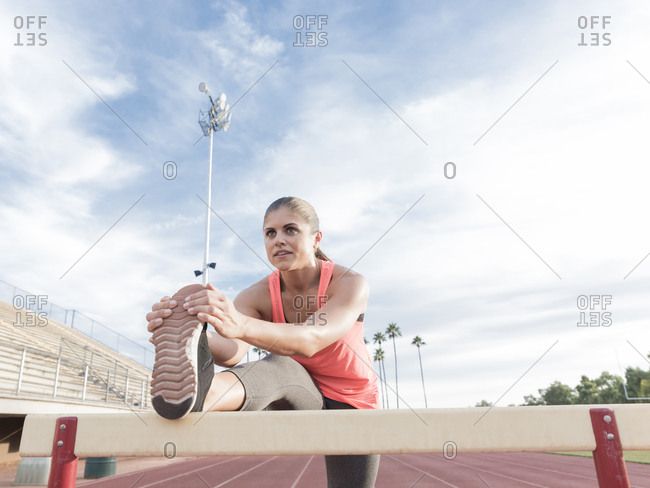 Hispanic woman stretching leg on hurdle
