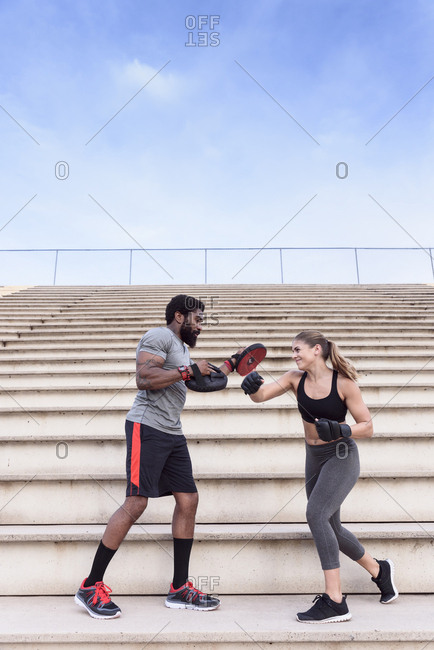 Trainer and woman boxing on bleachers
