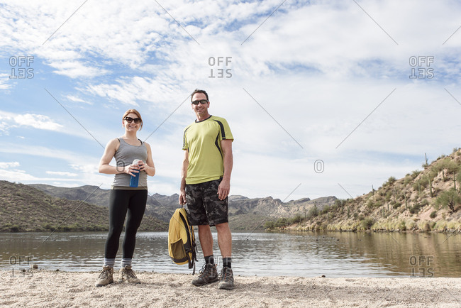 Portrait of smiling hikers standing at lake