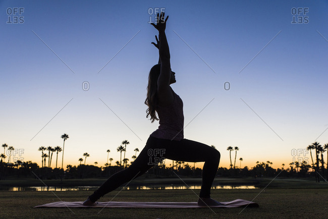 Silhouette of Hispanic woman performing yoga at sunset