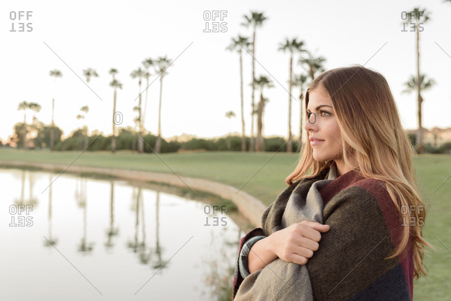 Pensive Hispanic woman near lake