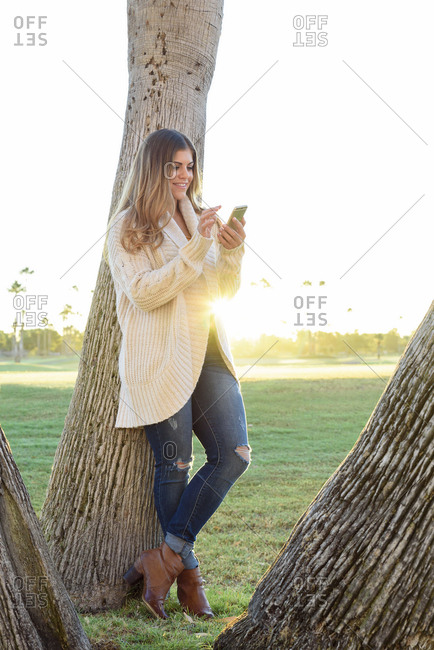 Hispanic woman leaning on tree texting on cell phone