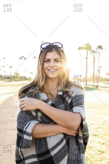 Smiling Hispanic woman wearing plaid poncho