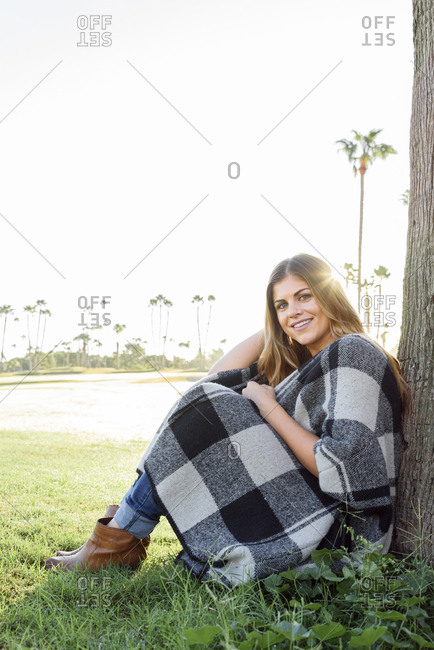 Hispanic woman leaning on tree