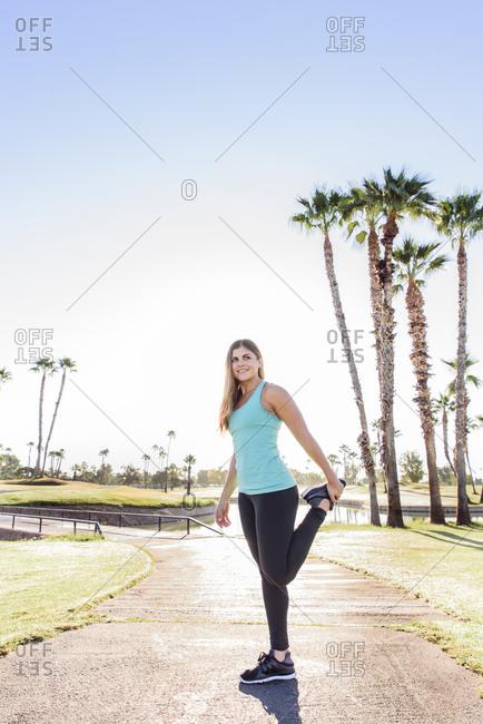 Hispanic woman stretching leg on path