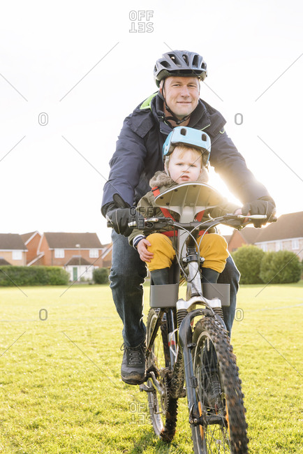 Caucasian father and son riding bicycle