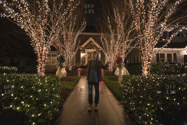Caucasian boy admiring Christmas decorations in yard