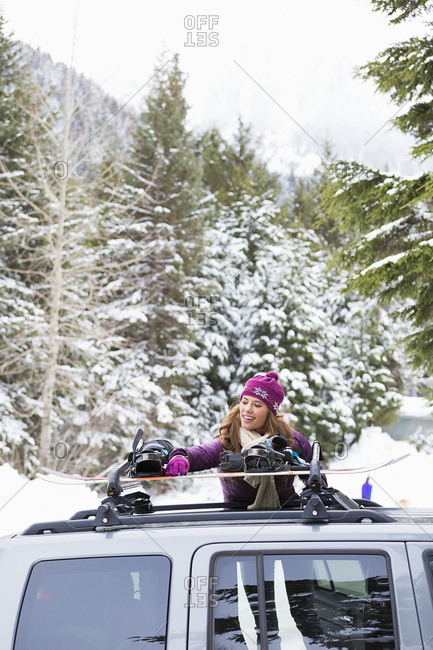 Caucasian woman checking snowboards in car roof rack