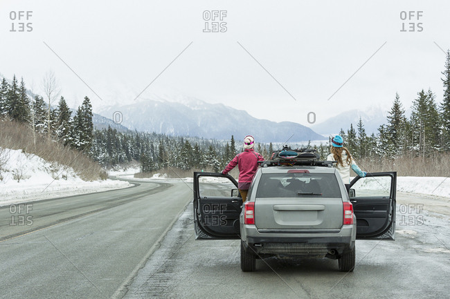 Caucasian women standing in car in winter admiring scenic view